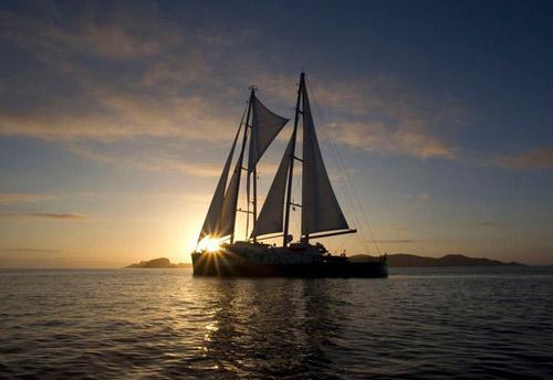 The new Rainbow Warrior sailing into Matauri Bay, New Zealand, at dawn